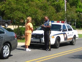 A uniformed police officer standing next to a patrol car writing on a pad while a woman talks to him